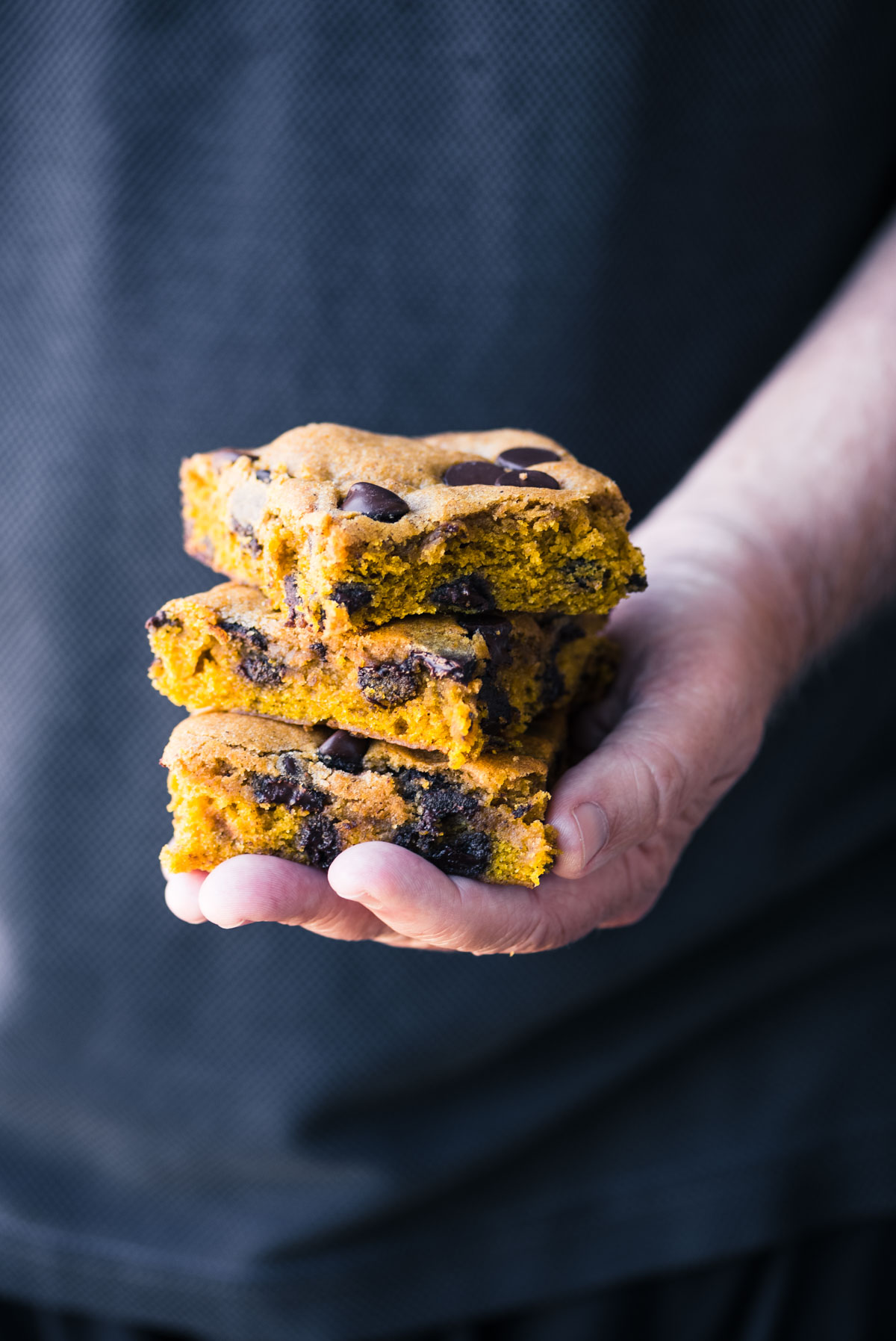 holding a stack of pumpkin chocolate chip blondies