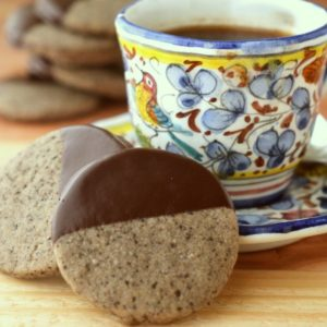 Photo of turkish coffee shortbread cookies dipped in chocolate next to a cup of coffee on a saucer.