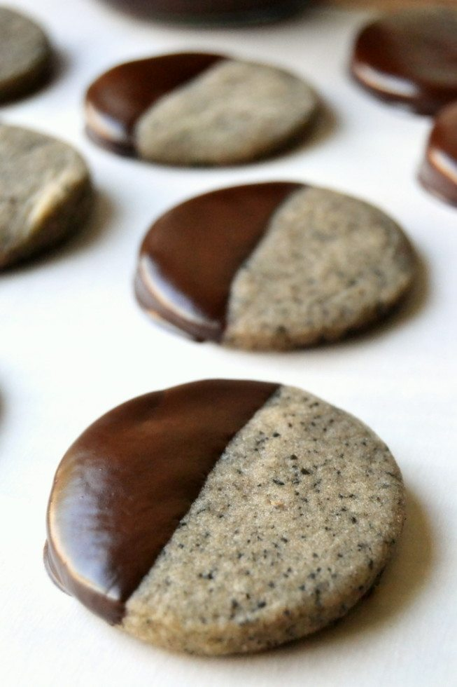 Photo of turkish coffee shortbread cookies dipped in chocolate laying on a piece of parchment paper.