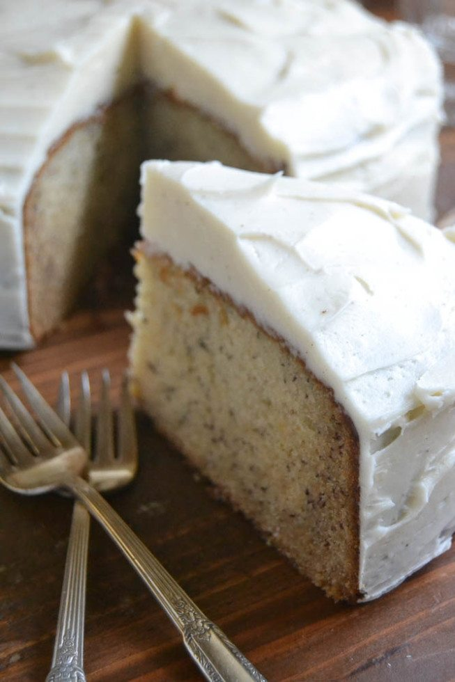 Photo of Banana Cake with Spiced Vanilla Buttercream with one slice removed and forks on a wooden surface.