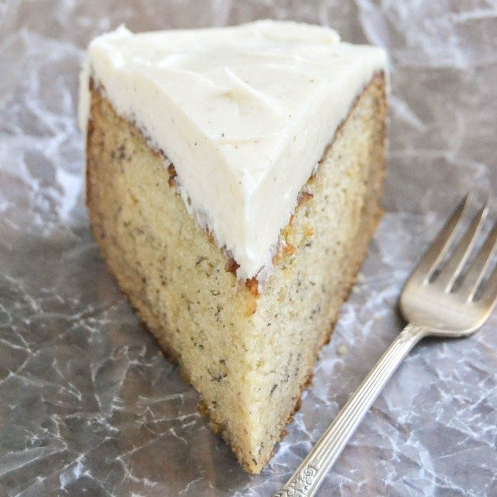 Phot of a single slice of Banana Cake with Spiced Vanilla Buttercream with a fork on parchment paper.
