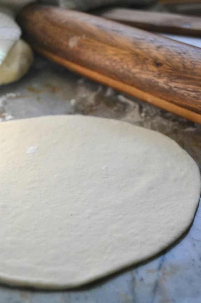 rolling out pita bread rounds