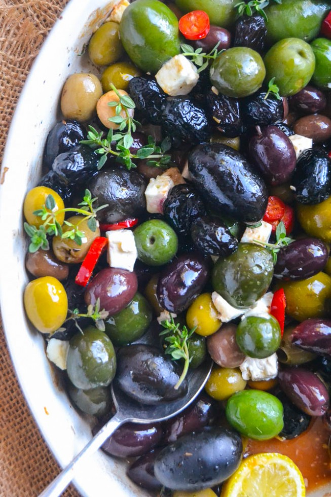 Easy roasted olives in a baking dish with spoon