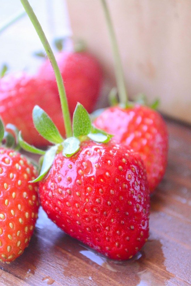 Close up photo of strawberries on a wood surface for easy chocolate dipped strawberries.