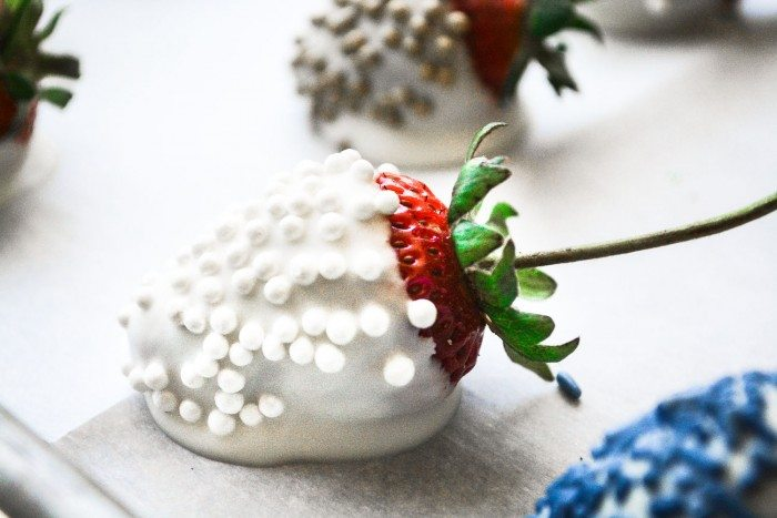 Close up photo of a strawberry dipped in white chocolate with white sprinkles on a white surface.