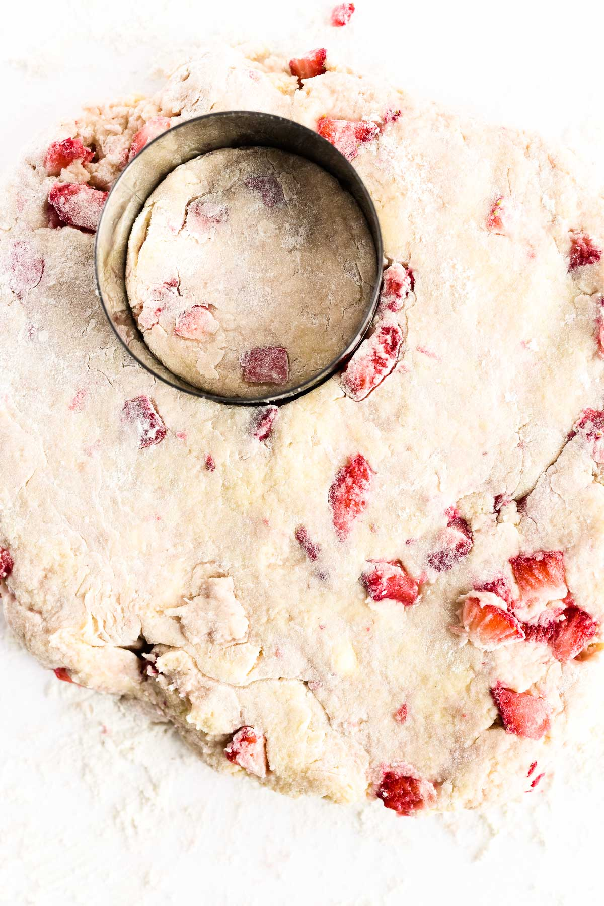 cutting out strawberry scones with a round biscuit cutter