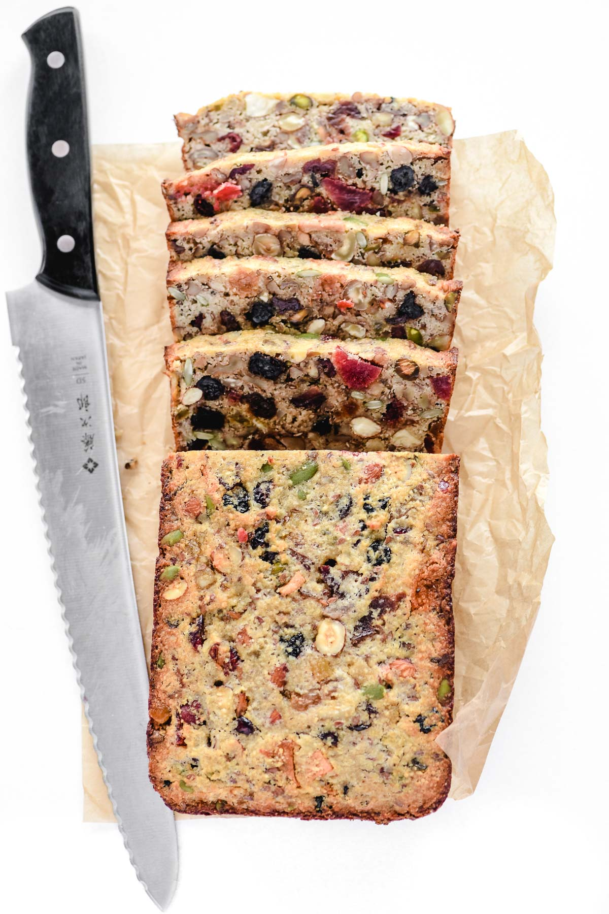 a loaf of paleo fruit and nut bread, sliced, with bread knife