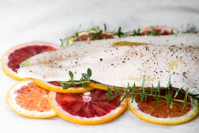 Healthy and low fat filet of fish with blood oranges and thyme in parchment