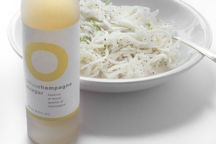 Photo of a bowl of sweet vidalia onion slaw next to a bottle of Citrus Champagne vinegar.