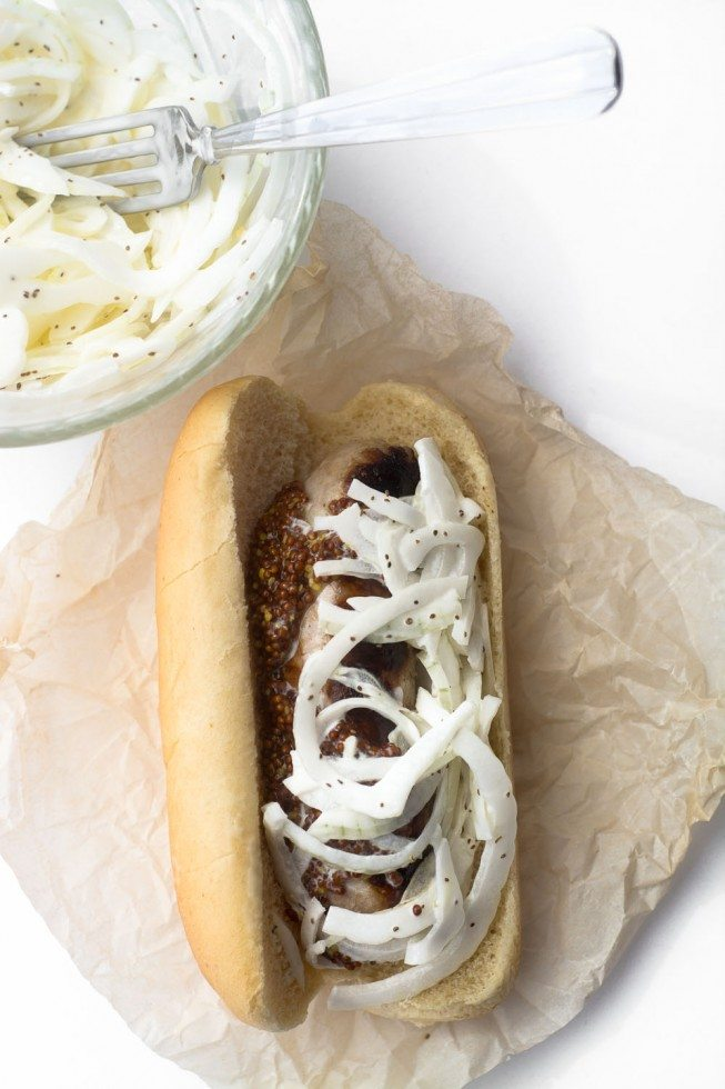 A bowl of sweet vidalia onion slaw, and a sausage in a bun topped with sweet vidalia onion slaw.