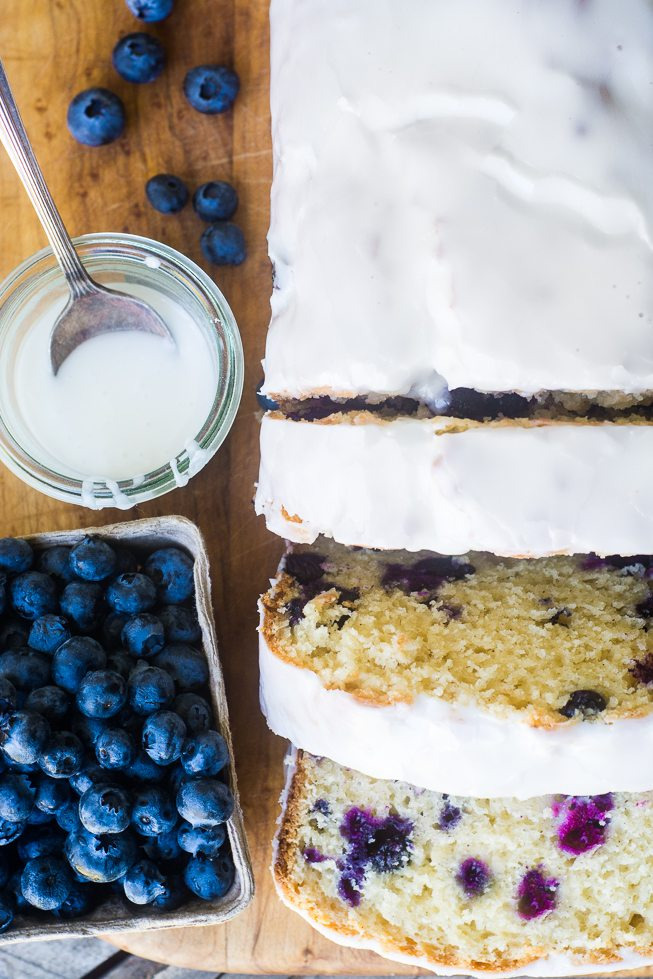A blueberry lemon pound cake with glaze and fresh blueberries