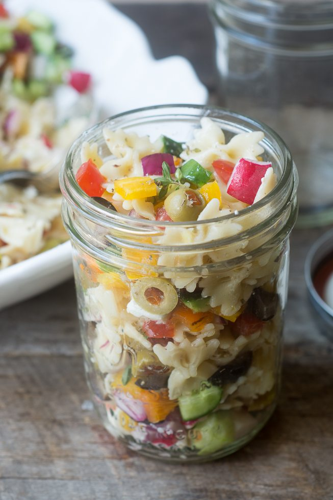 Photo of a small glass jar filled with israeli pasta salad on a wood surface.