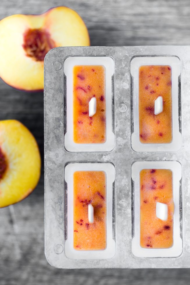 Overhead photo of ripe peach popsicles in popsicle molds against a gray wood surface.