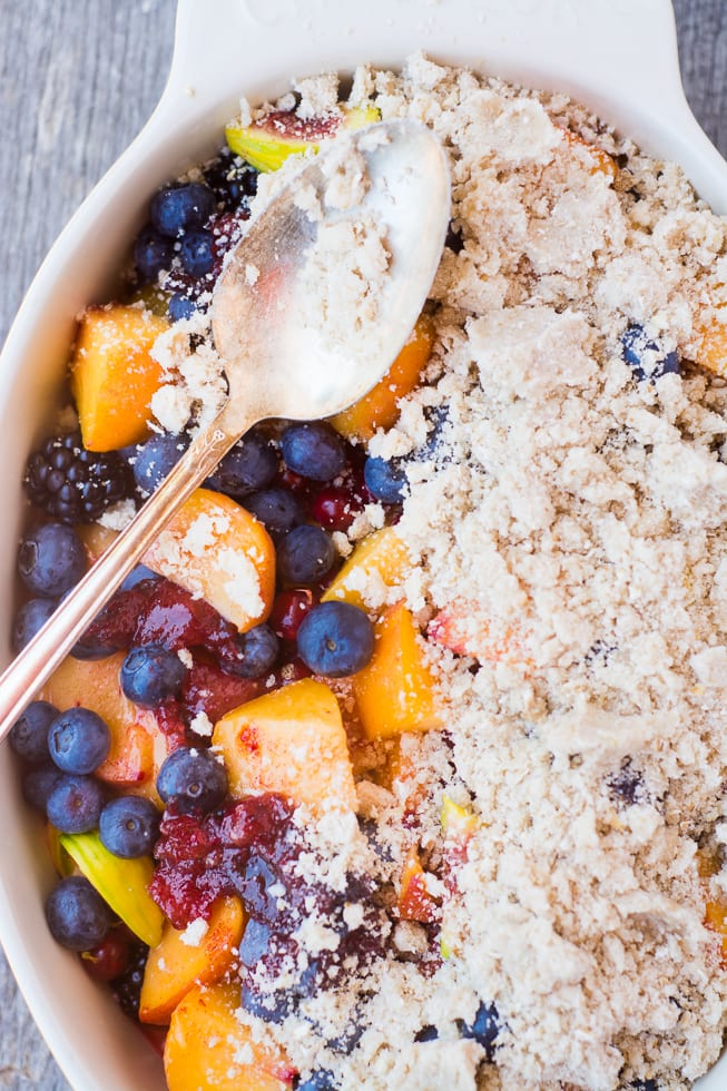 Mixed summer fruit crumble in a baking dish with spoon