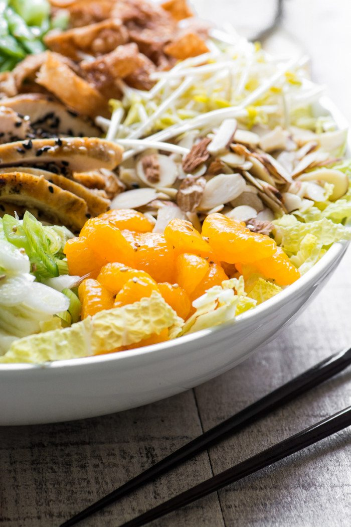 Side view photo of chinese chicken salad in a white bowl with black chopsticks.