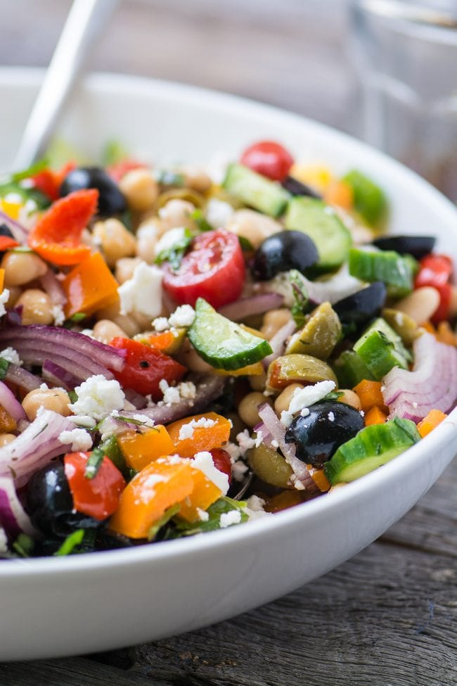 Mediterranean Bean Salad in a white bowl with spoon