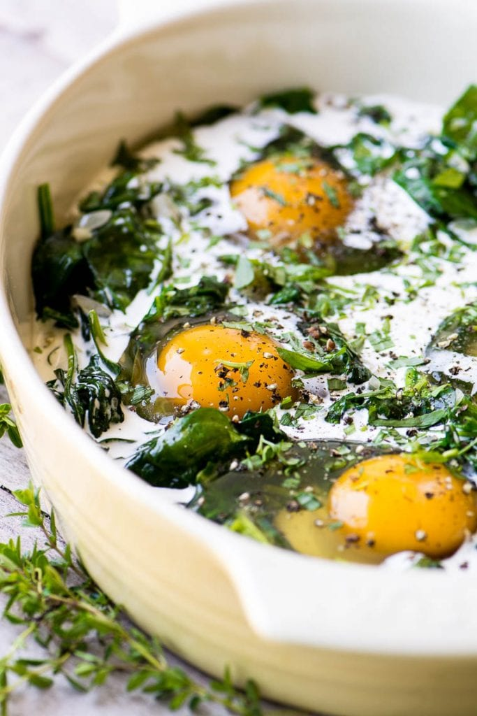 A gratin dish with Baked Eggs Florentine ready for the oven.