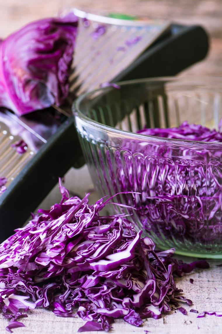 slicing red cabbage on a mandoline for red cabbage and dill slaw