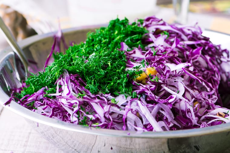 making red cabbage and dill slaw in a bowl