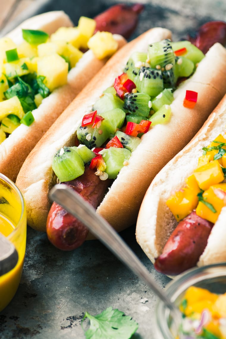 Hot dogs topped with homemade salsas and relishes for a tropical hot dog bar party