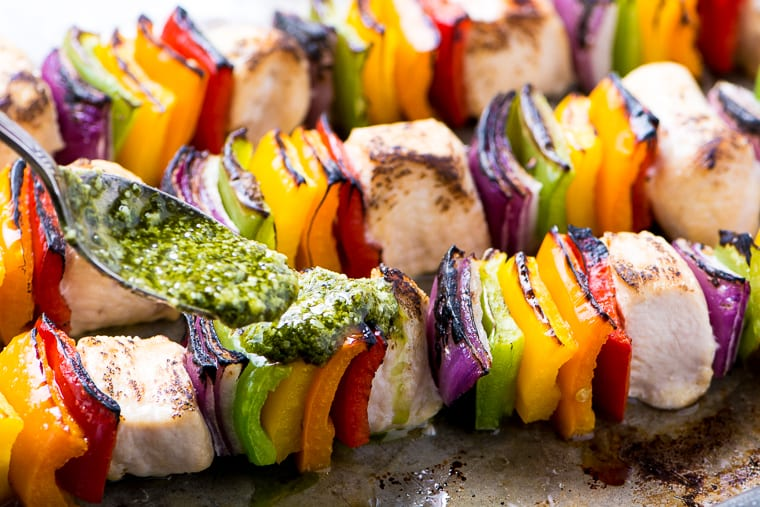 skewers of chicken and bell peppers with pesto being spooned over them.