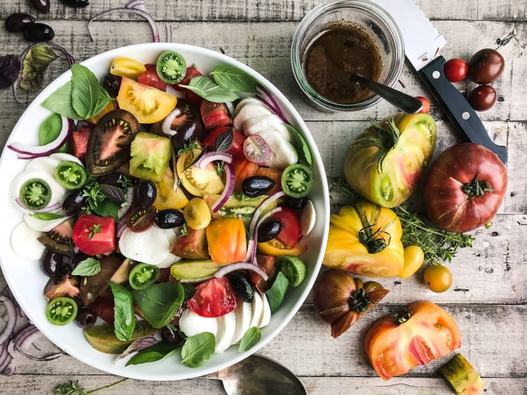 Making an heirloom Tomato Salad on a wooden table