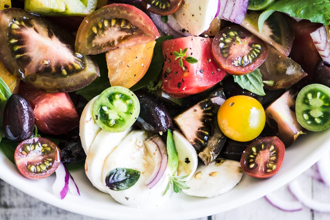Colorful heirloom tomato caprese salad in a white bowl