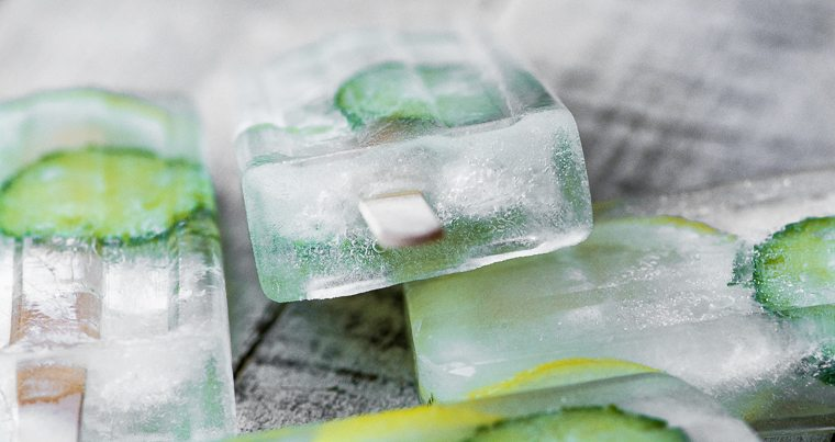 Close up photo of cucumber lemon spa popsicles on a gray wood surface.