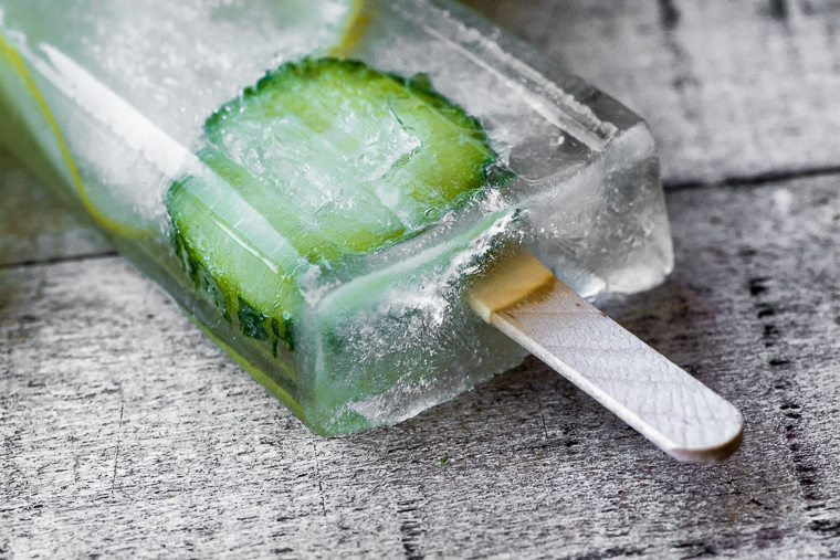 Close up photo of a cucumber lemon spa popsicle on a gray wood surface.