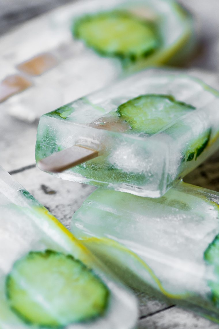 Photo of cucumber lemon spa popsicles stacked on a gray wood surface.