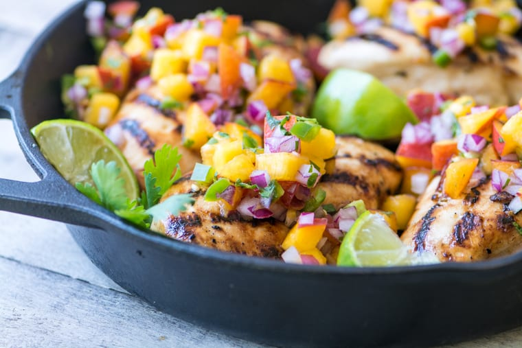 Grilled Chicken with Peach Jalapeño Salsa in a skillet with limes