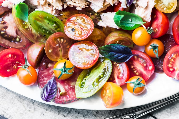 Summer tomato and tuna salad on a white platter