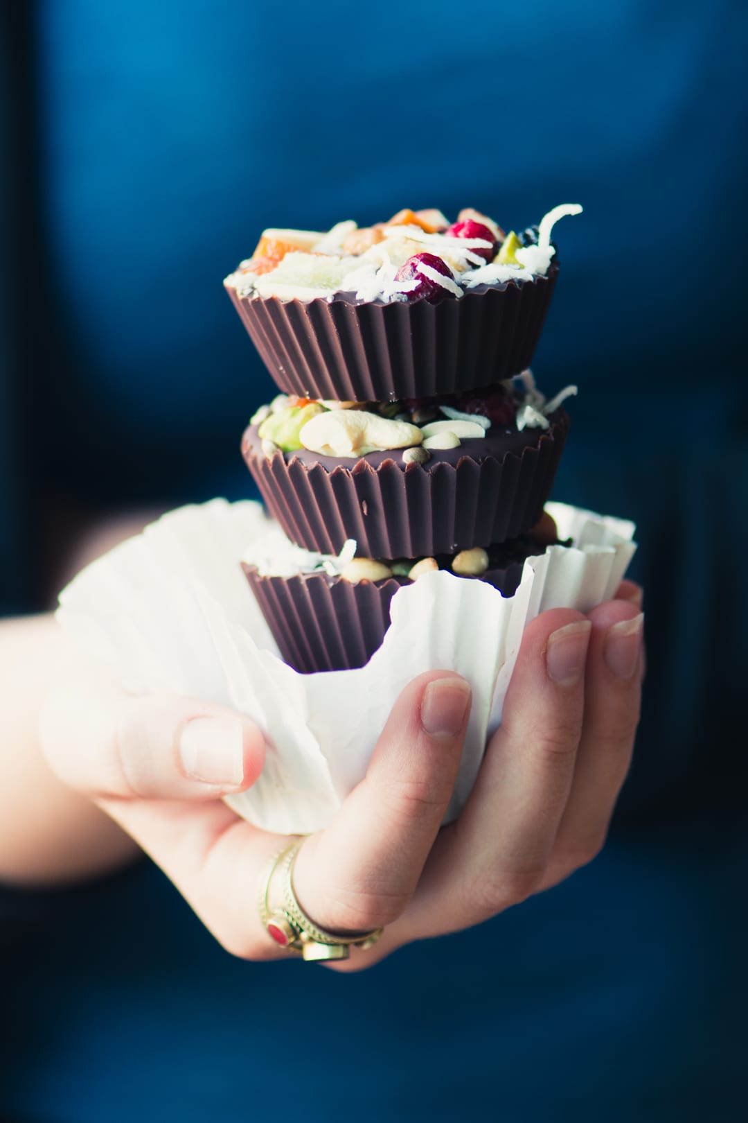 Hand holding a stack of Dark Chocolate Almond Butter Cups