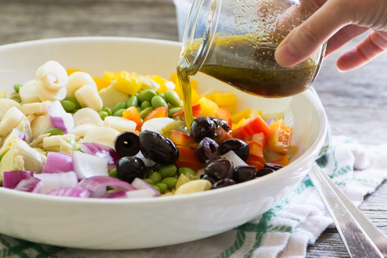Dressing a bowl of tortellini salad