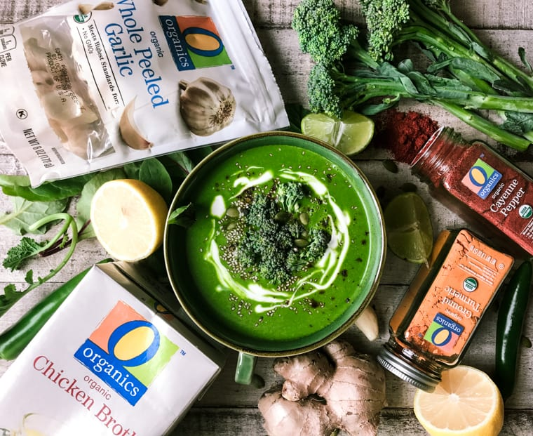 A mug of Green Goddess Immune Boosting Soup surrounded by ingredients.