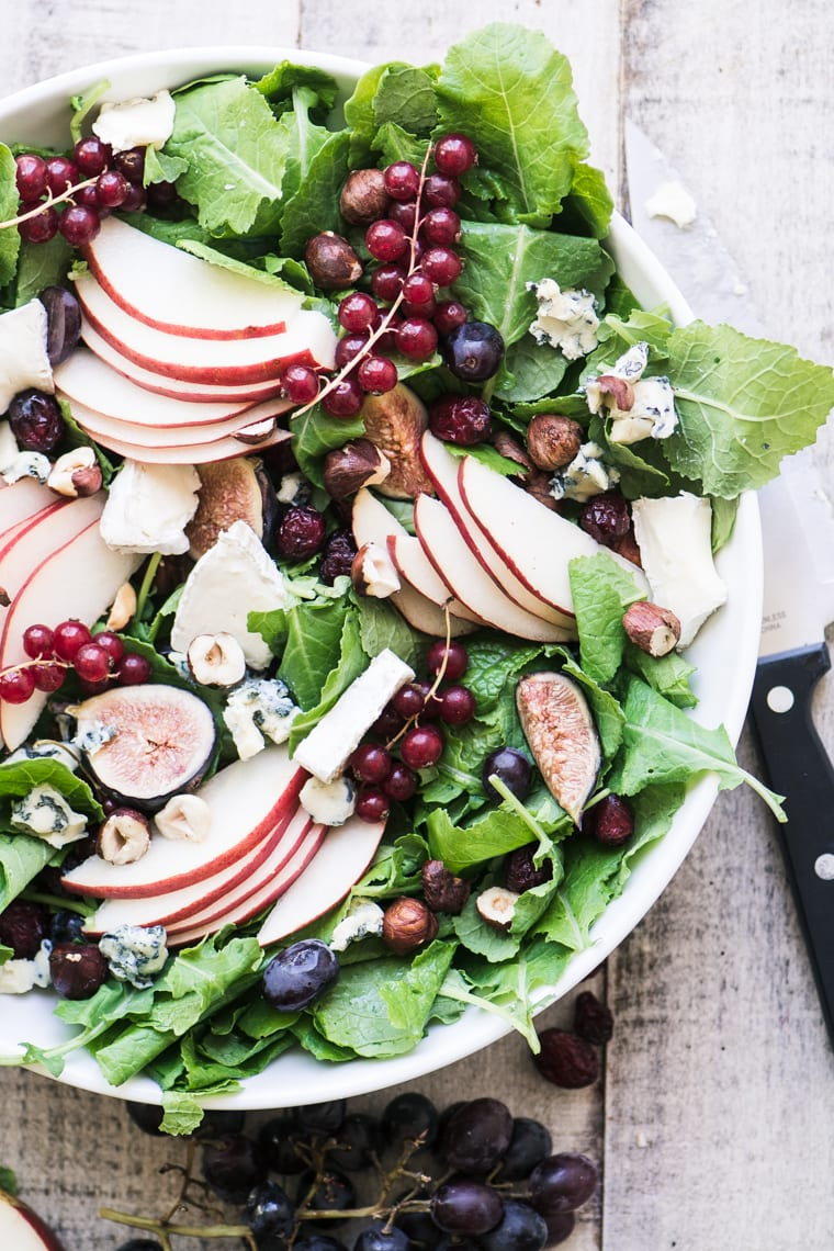 kale and fall fruit salad in a white bowl