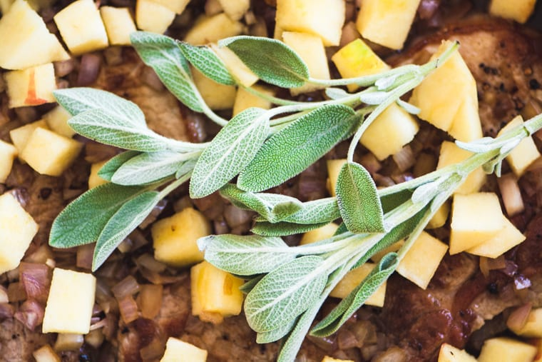 Sage leaves on top of ingredients for slow cooked apple bourbon smothered pork chops.