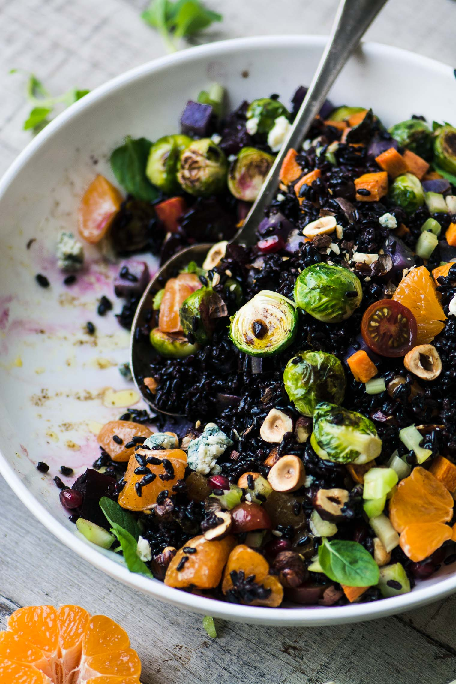 Black rice salad with roasted vegetables being tossed together in a white bowl.