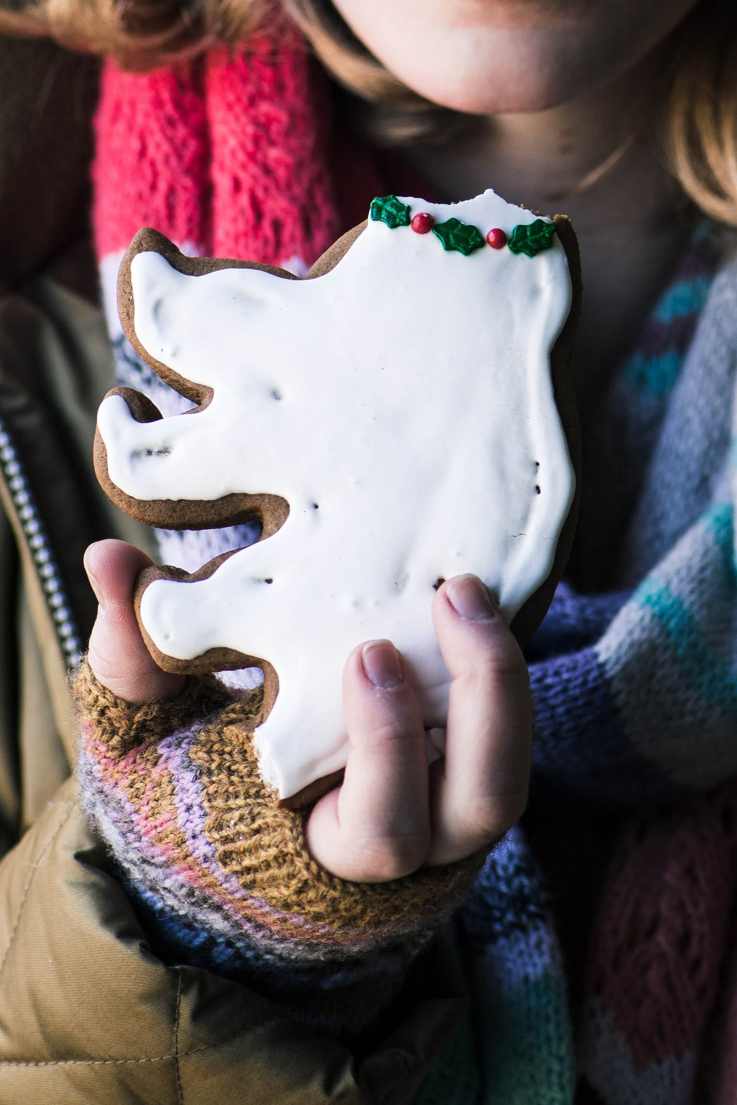 Girl eating the head off a Gingerbread Cookie with Royal Icing