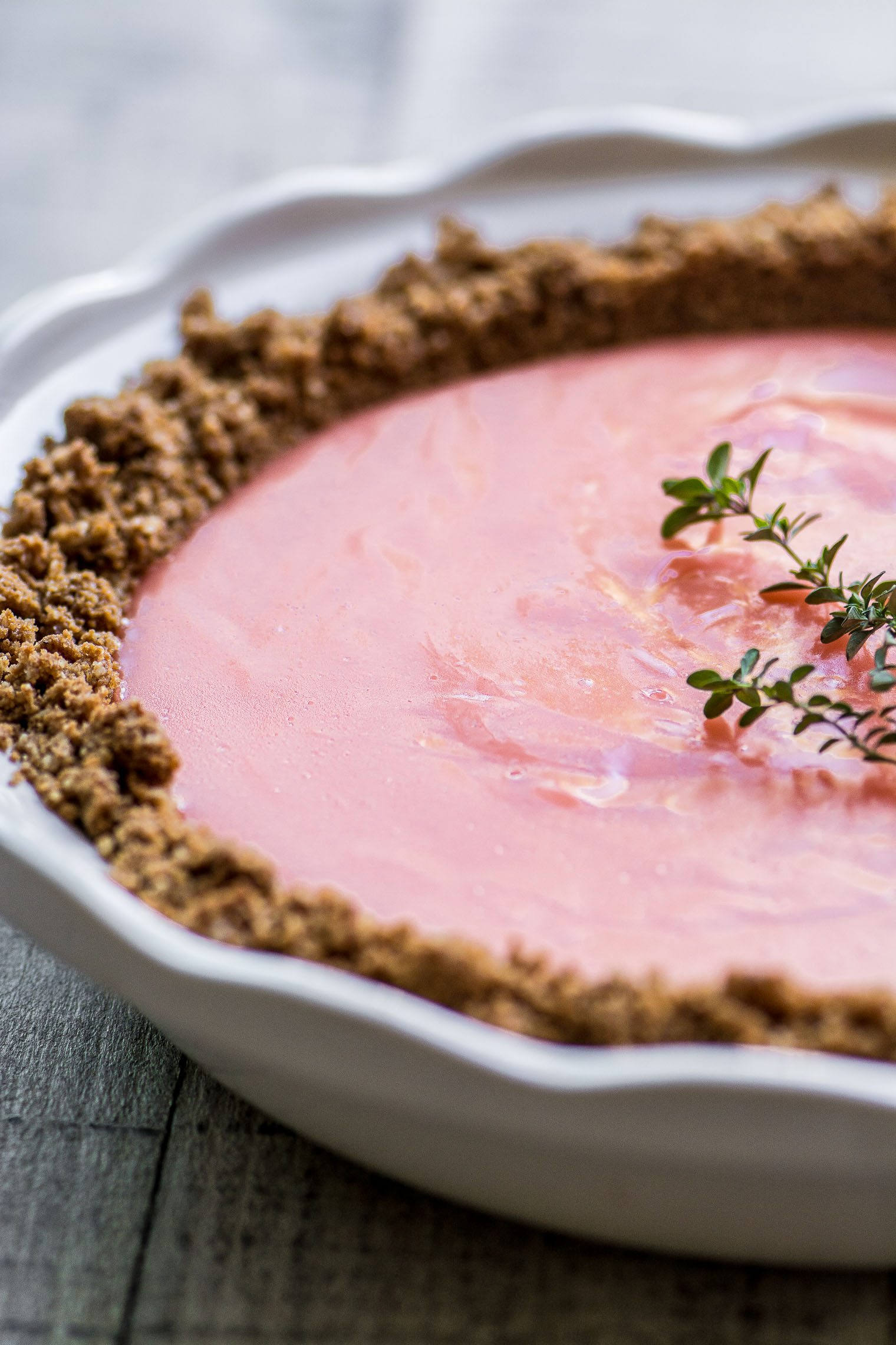 pink grapefruit gingersnap pie topped with thyme sprig
