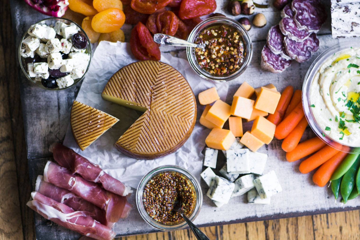 A cheese platter with cheese, meats, veggies, and fruit
