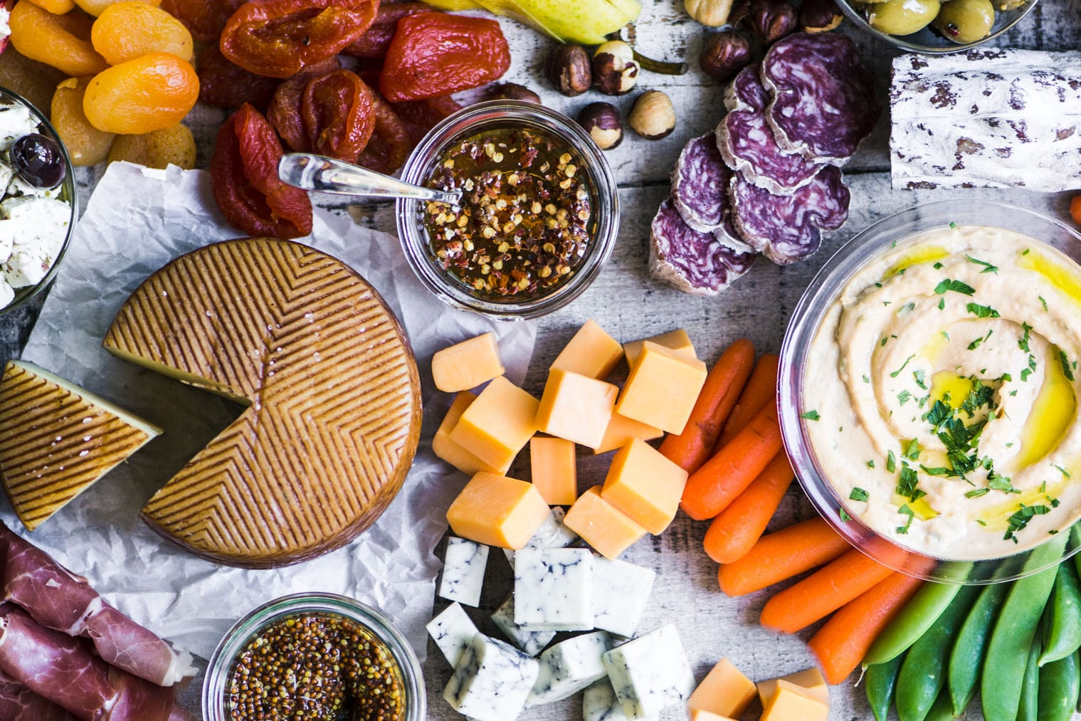 How to make the ultimate cheese board with meats, cheeses, dried fruits, and hummus.