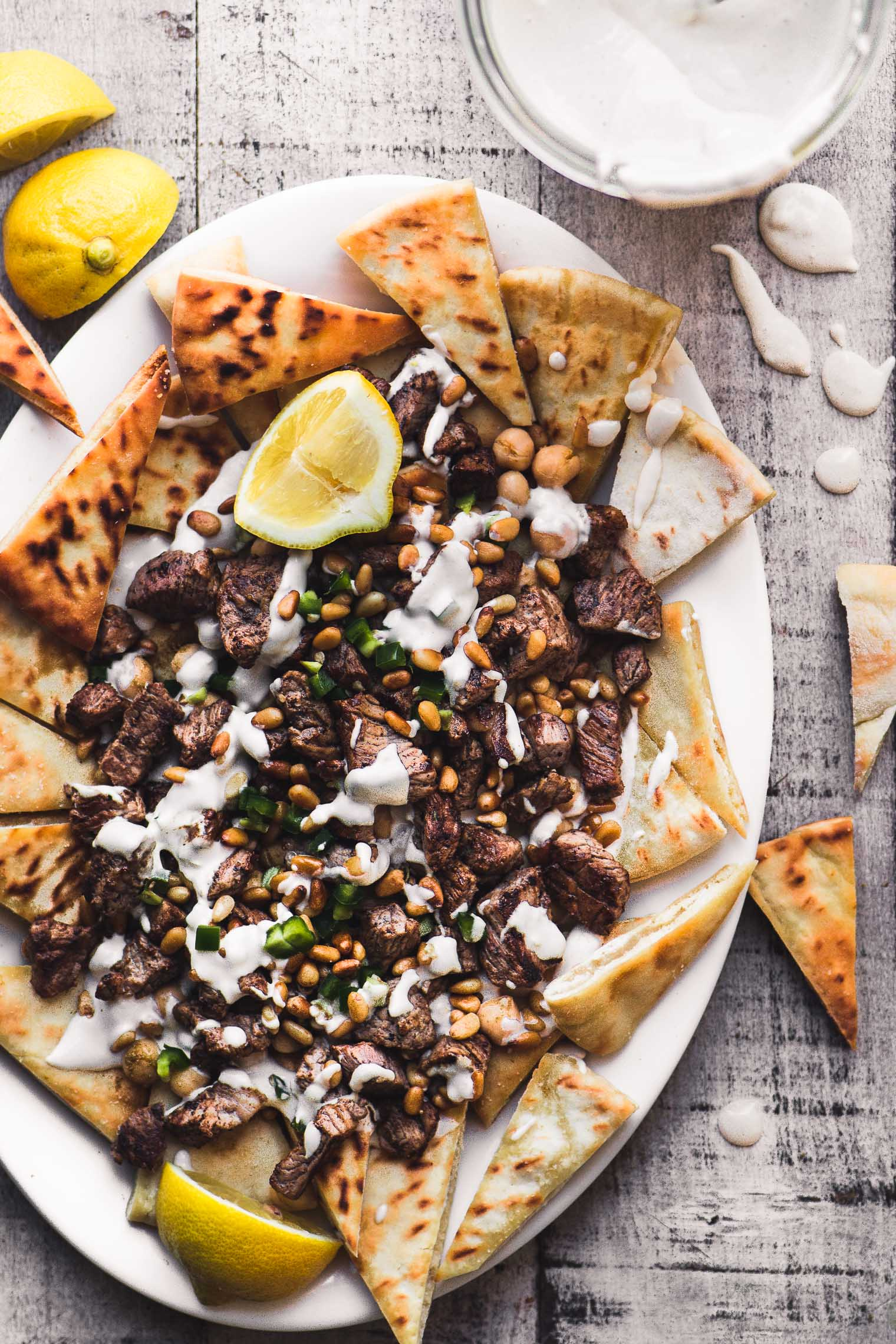 overhead photo of a plate of Middle Eastern Nachos with tahini sauce