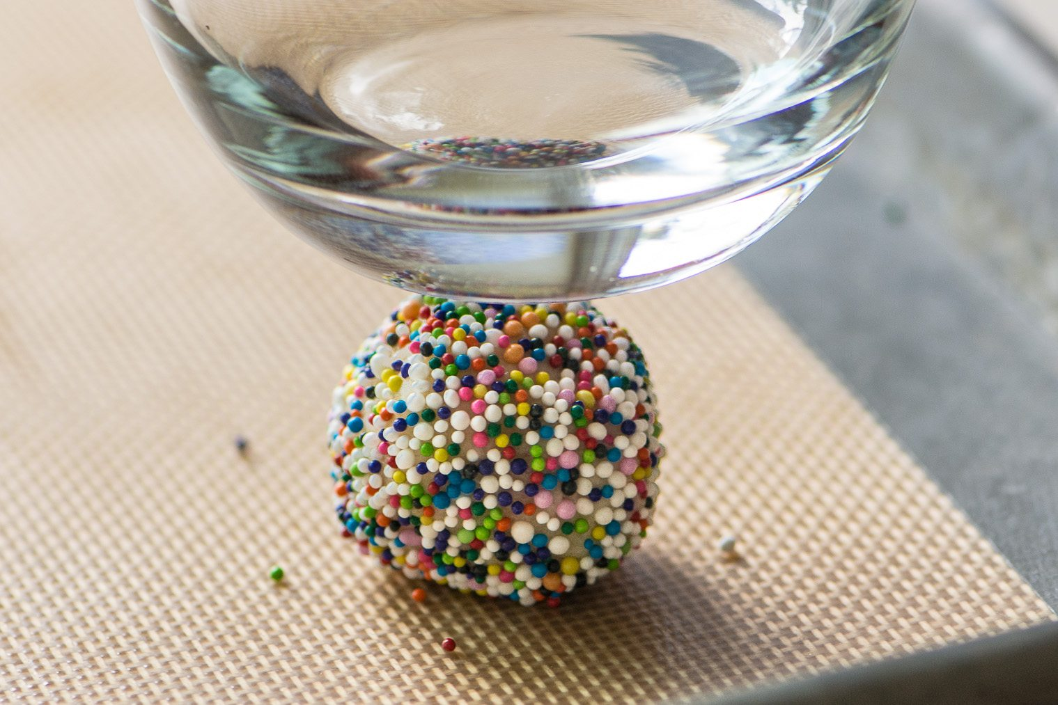 Flattening a Sprinkle Sugar Cookie with a glass, before baking