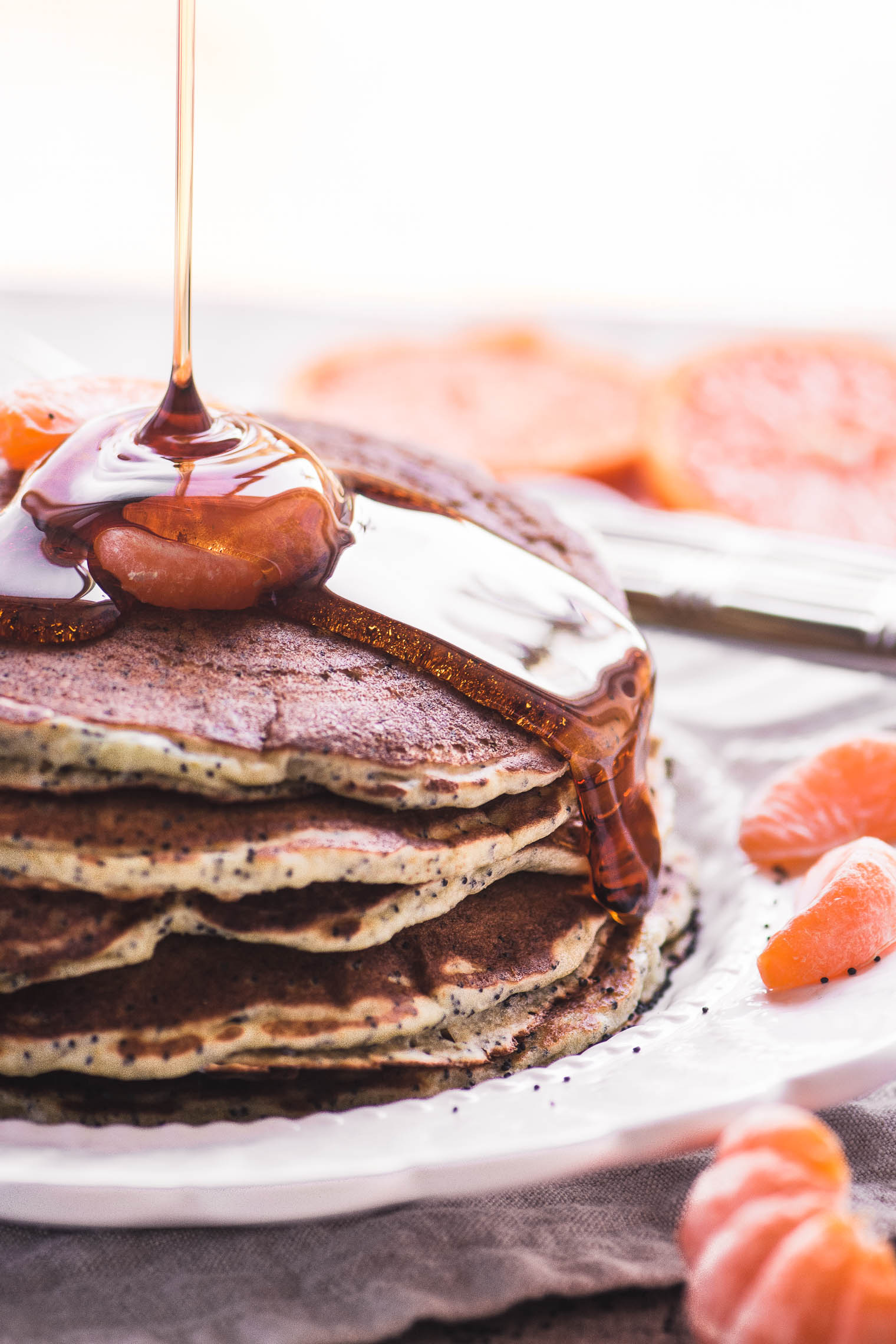 Pouring syrup on Tangerine Poppy Seed Pancakes
