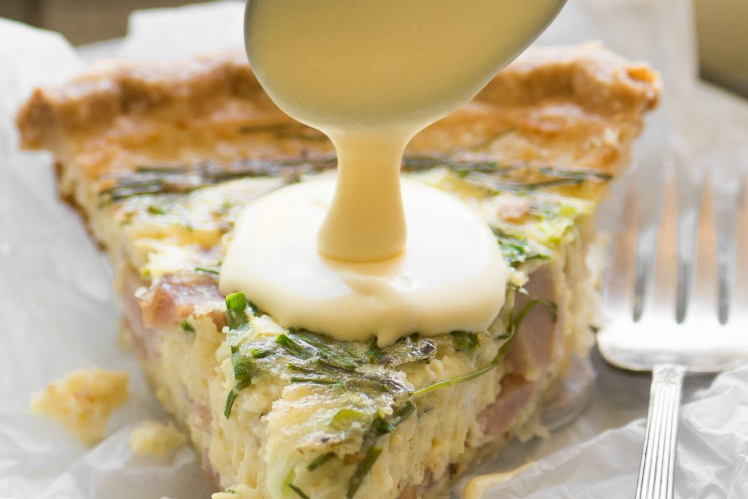 spooning hollandaise sauce on quiche