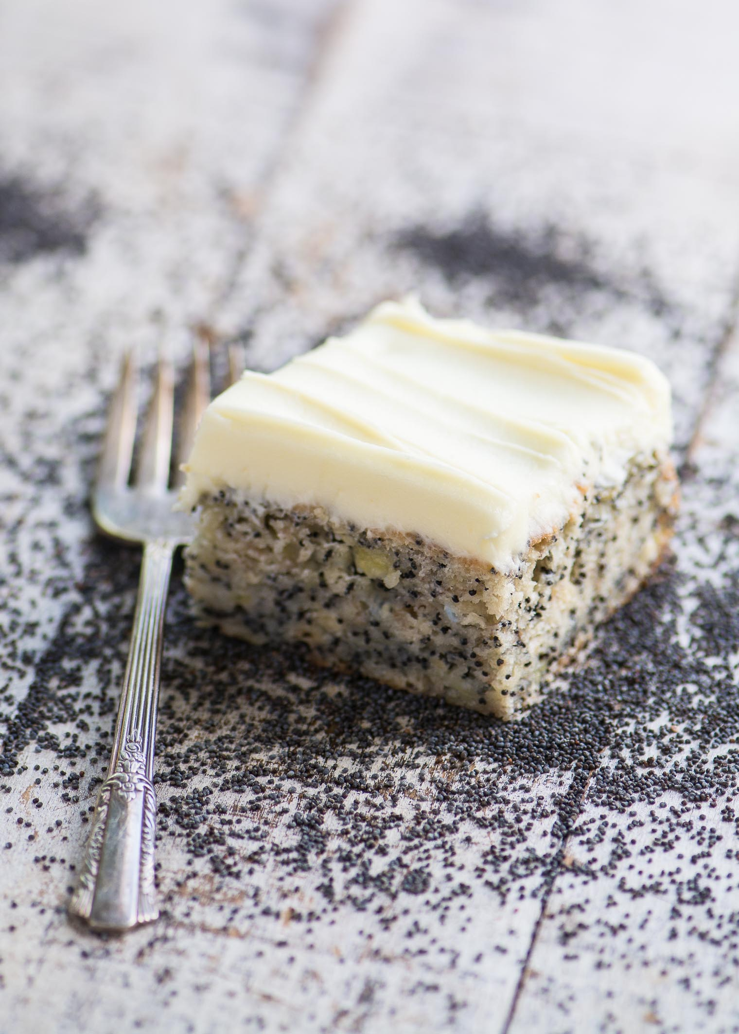 A piece of Banana Poppy Seed Cake with fork on a wooden table