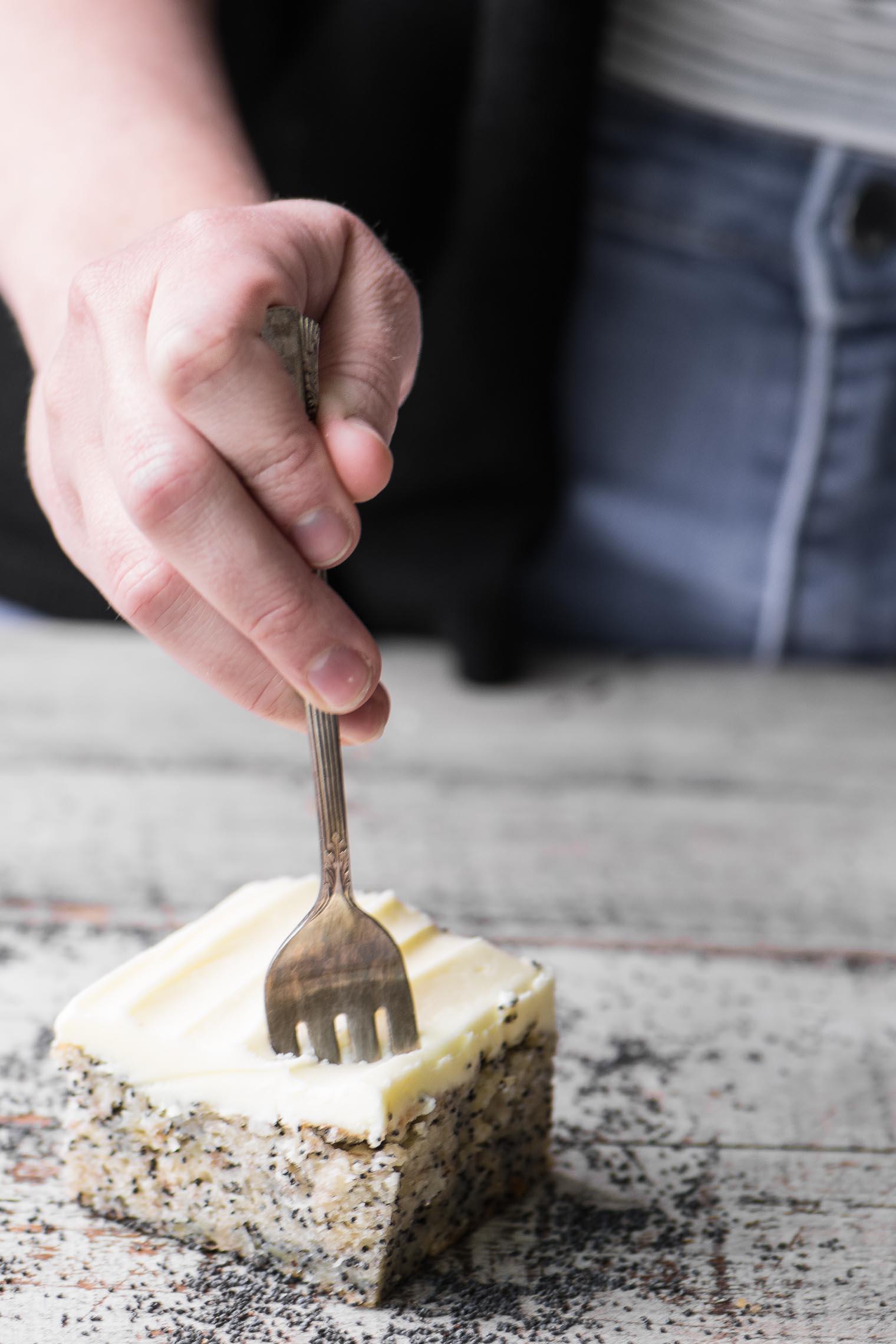 Banana Poppy Seed Cake with Lemon Buttercream on a wooden table