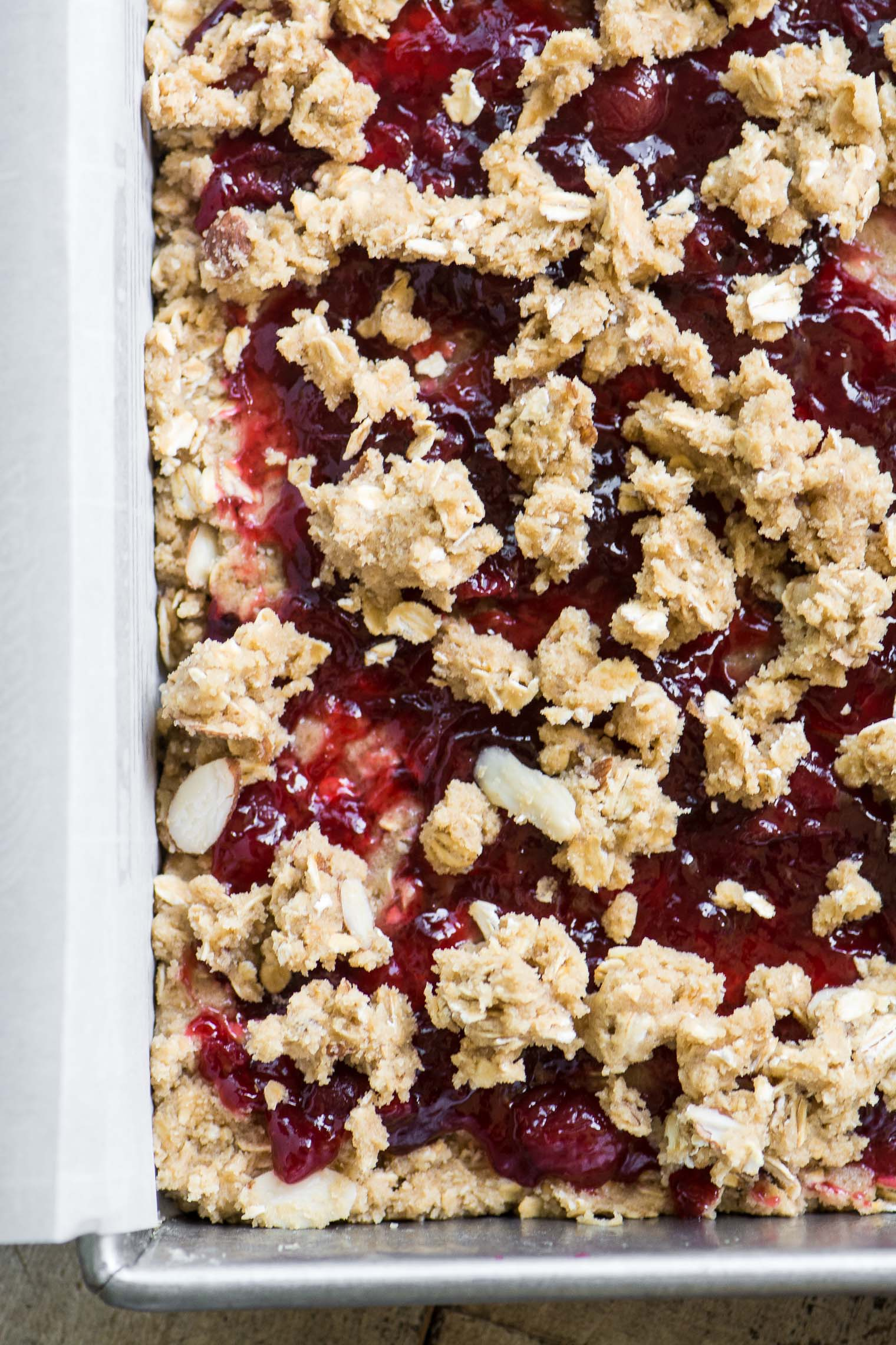 Sour almond cherry bars in a pan with parchment paper