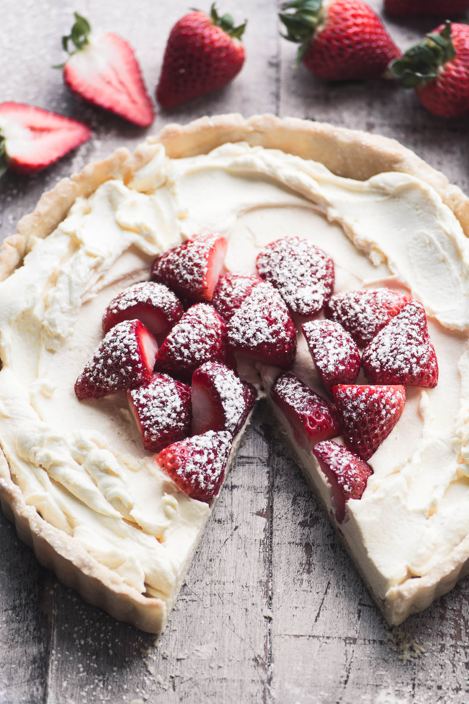 strawberries and cream tart with one piece cut from it, on wooden board